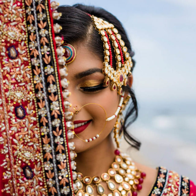 indian bridal portraits with red veil and jewelry