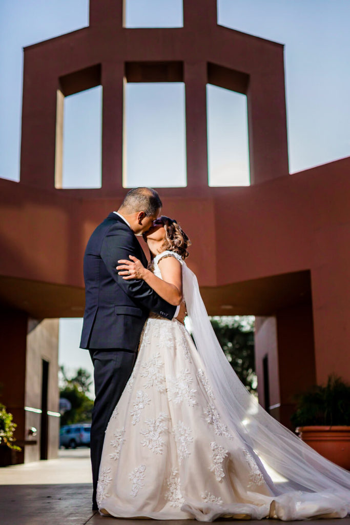 bride and groom portraits kissing in front of church