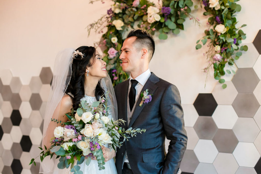 bride and groom portraits after wedding ceremony with floral arch